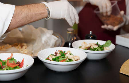 Chef is serving plates with salad in restaurant
