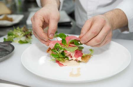 chef cocinando: El cocinero est� cocinando aperitivo en la cocina profesional Foto de archivo