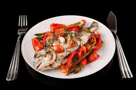 dorade: Roasted gilt-head bream with vegetables on plate isolated on black background