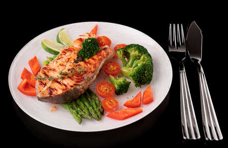gilthead bream: Roasted gilt-head bream with vegetables on plate, isolated on black background Stock Photo