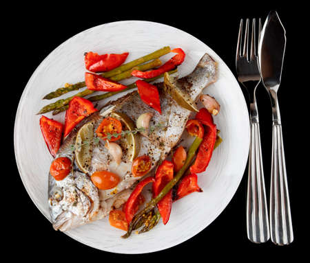 Roasted gilt-head bream with vegetables on plate, isolated on black background Stock Photo - 18028261