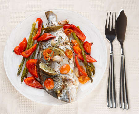 gilthead bream: Roasted gilt-head bream with vegetables in plate on table Stock Photo