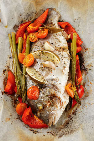 cooked fish: Gilt-head bream roasted with vegetables in paper, close-up
