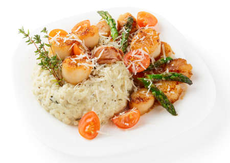 seared: Risotto with pan seared sea scallops, cheese and vegetables  isolated on white background