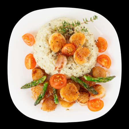 seared: Risotto with pan seared sea scallops isolated on black background