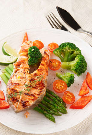 Grilled salmon steaks in plate on restaurant table photo