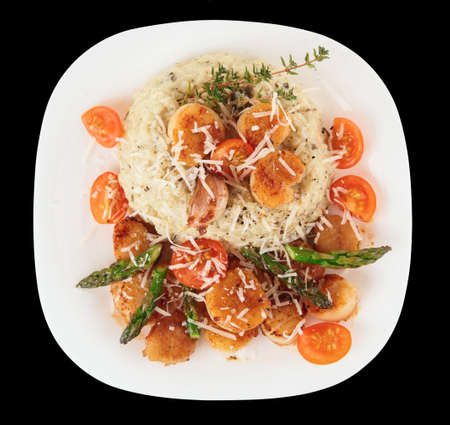 Risotto with pan seared sea scallops isolated on black background photo