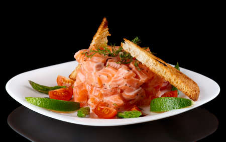 black dish: Salmon carpaccio in plate isolated on black background Stock Photo