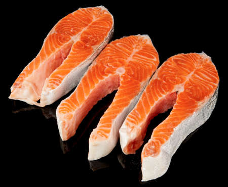 Three raw fresh salmon steaks isolated on black bacground photo