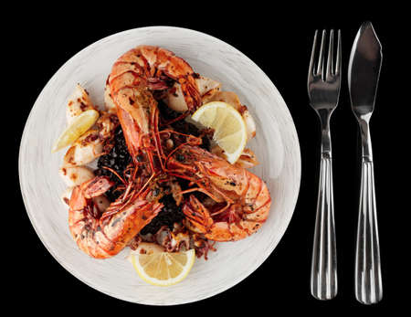 Jumbo prawns and grilled squids with black rice isolated on black background photo