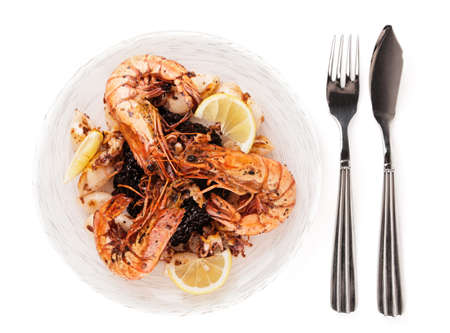 Jumbo prawns and grilled squids with black rice isolated on white background photo