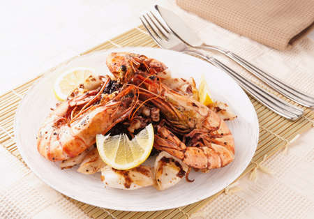 Jumbo prawns and grilled squids with black rice on restaurant table photo
