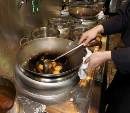 Doughnuts being fried in oil in wok pan, asian restaurant photo