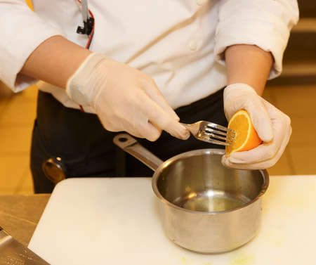 sautee: Chef is squeezing orangeto make sauce at restaurant kitchen