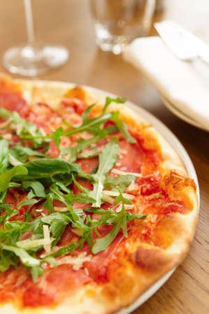 Pizza met rucola op restaurant tafel Stockfoto