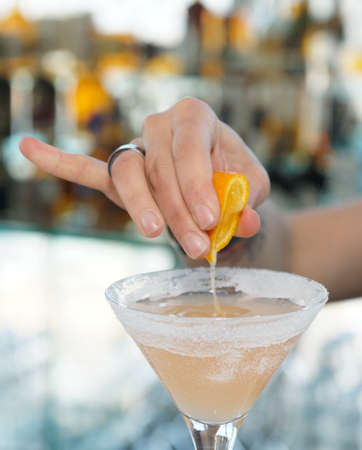 Female bartender is squeezing orange juice into a cocktail glass photo