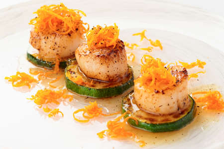 seared: Fried sea scallops with orange zest in plate