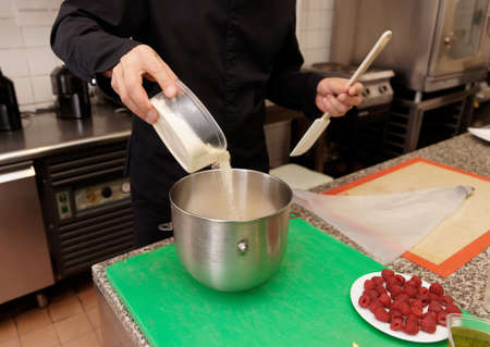 Pastry chef is pouring flour in a mixing bowl photo