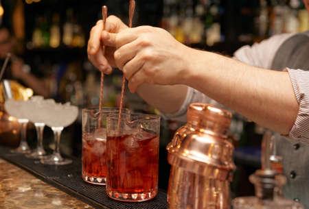 Barman is roeren cocktails op staafteller Stockfoto