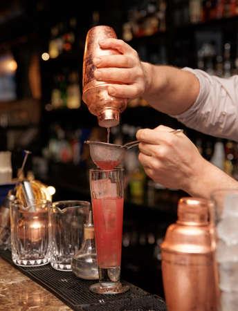 highball: Bartender is straining cocktail in highball glass