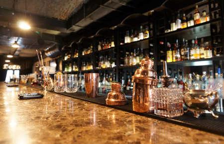 botella de licor: Barra de bar clásico con botellas en el fondo borroso