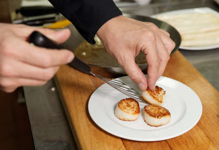 seared: Chef is serving seared scallops on plate Stock Photo