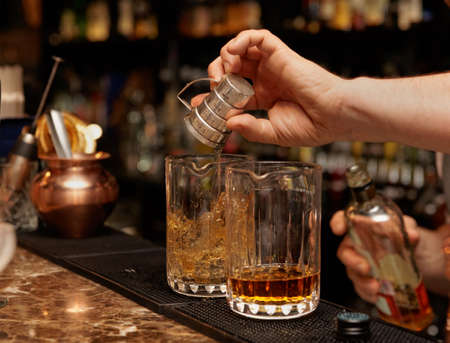 Bartender is pouring whisky in glass on the bar counter Stock Photo