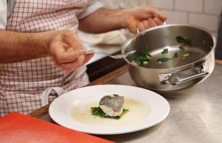 seabass: Chef est� sirviendo lubina al vapor con espinacas Foto de archivo
