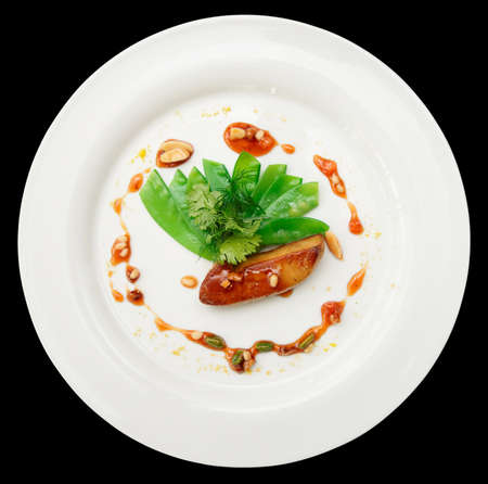 Fried foie gras with caramel and vegetables on plate, isolated on black background