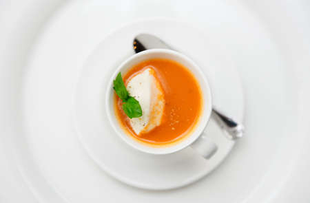 Small snack - gazpacho soup served in coffee cup with whipped cream photo
