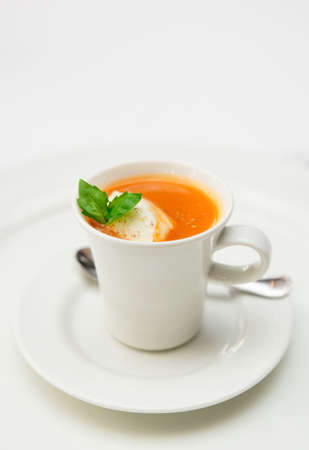 Gaspacho soup served in coffee cup with whipped cream and basil leaf photo