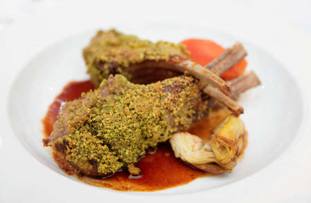 italian cusine: Grilled rack of lamb with mint and pistachio on plate  Stock Photo