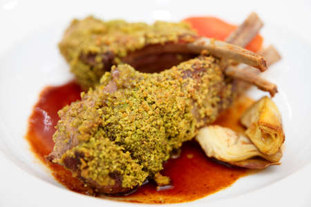 italian cusine: Grilled rack of lamb with pistachio and artichokes on plate, close-up