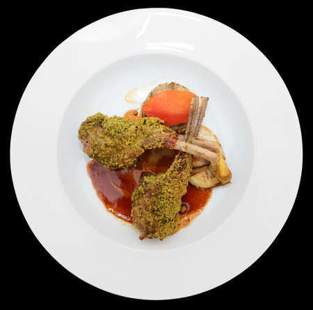 italian cusine: Grilled rack of lamb with pistachio in plate, isolated on black background