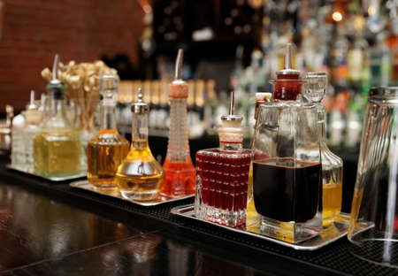Bitters and infusions on bar counter, bar bottles in blurred background Foto de archivo
