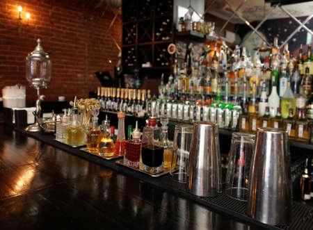 botella de whisky: Bitters e infusiones en barra de bar con botellas borrosa en el fondo