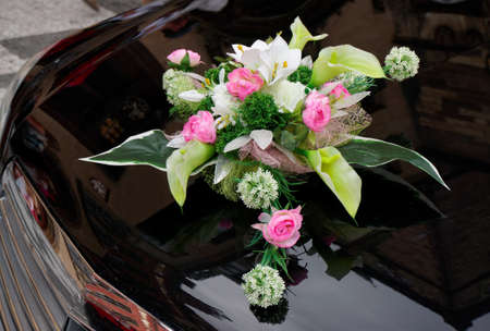 cowl: Wedding boquet on expensive black car cowl Stock Photo
