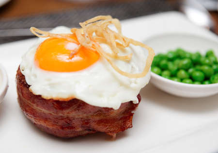 british cuisine: Tenderloin steak with fried egg and green pies, british cuisine dish