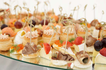 Small fish, meat and cheese snacks in plate on banquet table close-up photo