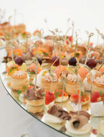 Small fish, meat and cheese snacks in plate on banquet table photo