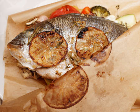 gilthead bream: Gilt-head bream roasted with vegetables and lemon in paper, close-up