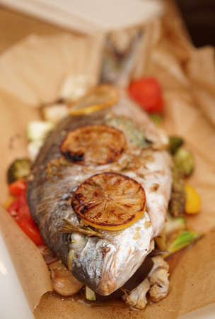 Dorade roasted with vegetables and lemon in paper, close-up photo