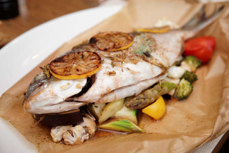 gilthead bream: Gilt-head bream roasted with vegetables and lemon in paper, close-up Stock Photo