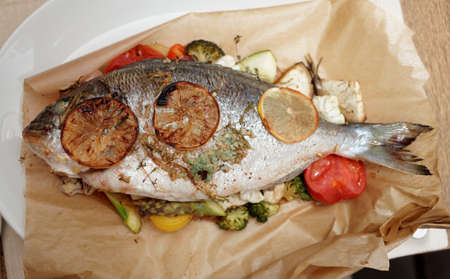 Gilt-head bream roasted with vegetables and lemon in paper, close-up Stock Photo - 22086785