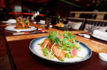 restaurant food: Appetizer with rare fried tuna and salmon on restaurant table