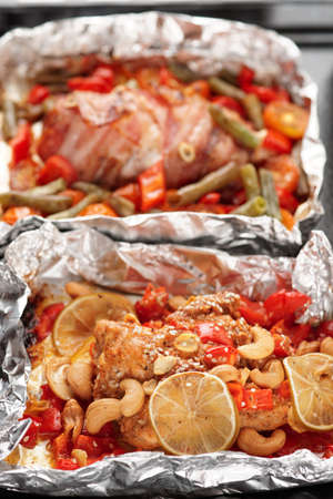 Two cooked chicken dishes in foil photo