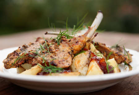 rack of lamb: Grilled rack of lamb with fried potatoes and onion chutnee shot outdoors Stock Photo