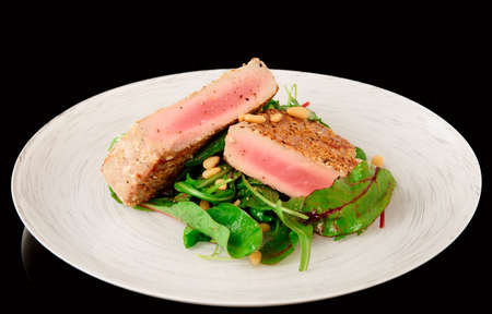 ahi: Lightly seared tuna steak and fresh salad isolated on black