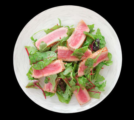 ahi: Appetizer with rare fried tuna in plate isolated on black background Stock Photo