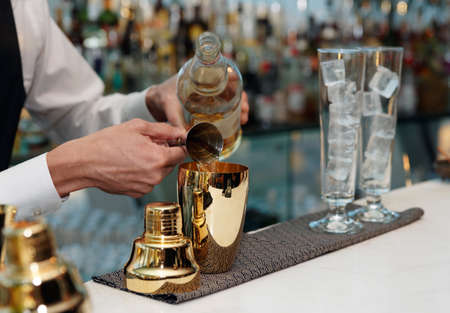 Bartender is pouring liquor in golden shaker Foto de archivo